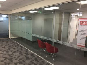Client waiting area and meeting room with branding in film on glass